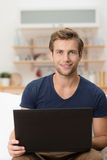 Young male student working on a laptop. Young handsome male student working on a laptop computer at home in the living room giving the camera a friendly smile Royalty Free Stock Photography