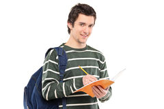 Young male student writing in a notebook. Isolated on white background Stock Images
