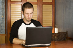 Young male studying on laptop. With serious face Stock Photography