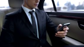 Young male in suit texting on smartphone while riding in personal business car royalty free stock images