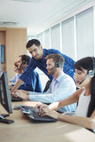 Young male supervisor assisting telemarketer at call center. Young male supervisor assisting telemarketer at desk in call center Royalty Free Stock Image