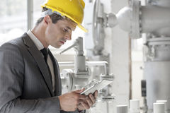 Young male supervisor using tablet PC in industry Stock Photos