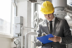 Young male supervisor writing on clipboard in industry Stock Image