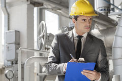 Young male supervisor writing on clipboard in industry Royalty Free Stock Photos