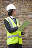 Young male supervisor writing notes at construction site Stock Photo