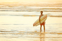 Young male surfer at the beach for sunrise with surfboard. Wide shot of man holding surfboard standing in the water of the shallow surf on the beach early in the Royalty Free Stock Image