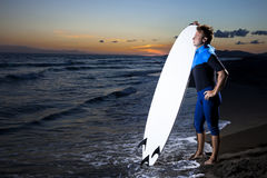 Young male surfer  on  beach in sunset. Young surfer with board looking at sunset on sandy beach Stock Photos