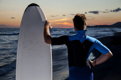 Young male surfer  on  beach in sunset. Young surfer with board looking at sunset on sandy beach Stock Photo