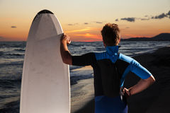 Young male surfer  on  beach in sunset. Young surfer with board looking at sunset on sandy beach Royalty Free Stock Photo