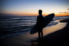 Young male surfer  on  beach in sunset. Silhouette of young male surfer holding board on sandy beach in sunset Royalty Free Stock Image