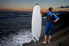 Young male surfer  on  beach in sunset Stock Images