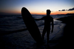 Young male surfer  on  beach in sunset. Silhouette of young male surfer holding board on sandy beach in sunset Royalty Free Stock Photos