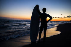 Young male surfer on beach in sunset. Silhouette of young male surfer holding board on sandy beach in sunset Stock Photography