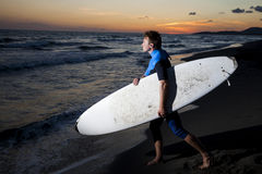 Young male surfer  on  beach in sunset. Young surfer in wetsuit going in the water with board on sandy beach in sunset Royalty Free Stock Photography