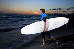 Young male surfer  on  beach in sunset. Young surfer in wetsuit going in the water with board on sandy beach in sunset Royalty Free Stock Image