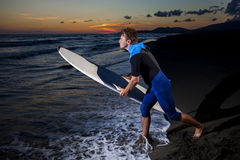 Young male surfer  on  beach in sunset. Young surfer in wetsuit going in the water with board on sandy beach in sunset Stock Photos