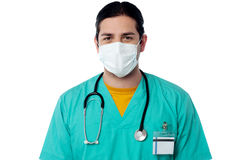 Young male surgeon wearing a face mask. Male physician covering face with surgical mask stock image