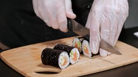 Young male sushi chef prepares Japanese sushi rolls of rice, salmon, avocado and nori. Restaurant kitchen, closeup hands stock video footage