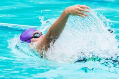 Young male swimmer swims in back stroke. Chiang Mai, Thailand - 11 October 2017 - young male swimmer swims in back stroke at a school swimming pool in Chiang Mai Stock Image