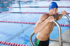 Young male swimmer using ladder to exit swimming pool Stock Photos