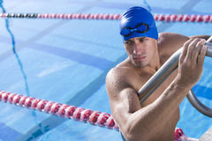 Young male swimmer using ladder to exit swimming pool Royalty Free Stock Photos