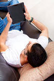 Young male with tablet on a couch Stock Images