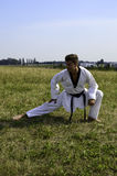 Young male taekwondo fighter stretching Royalty Free Stock Image