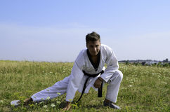 Young male taekwondo fighter stretching Stock Photography