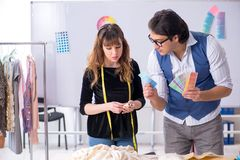 Young male tailor teaching female student stock photo