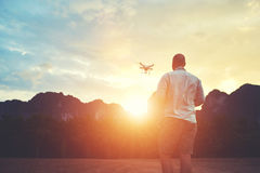 Young male is taking photo on modern flying remote camera during summer trip Stock Image