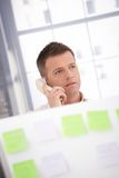 Young male talking on phone in office. Young male office worker talking on phone behind partition Royalty Free Stock Photos