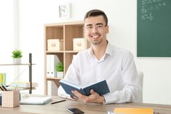 Young male teacher with book sitting at table. In classroom Stock Image