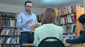 Young male teacher with book talking to students in library stock video footage