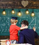 Young male teacher guides his child student to learning while boy hugs teacher, sitting in classroom, chalkboard with. Scribbles on backgraund, rear view Royalty Free Stock Image