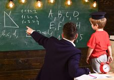 Young male teacher guides his child student to learning while pointing and looking at chalkboard with scribbles on. Sitting in classroom, rear view Royalty Free Stock Images