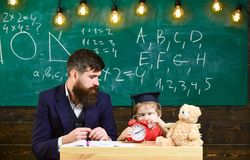 Young male teacher guides his child student to learning while sitting in classroom with scribbles on chalkboar. D Royalty Free Stock Photos