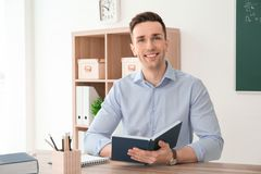 Young male teacher with notebook sitting at table. In classroom Royalty Free Stock Photo