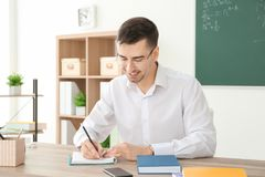 Young male teacher working at table. In classroom Royalty Free Stock Images