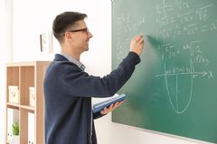 Young male teacher writing on blackboard. In classroom Stock Photos