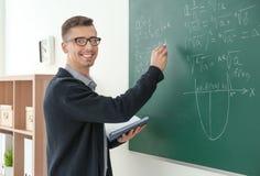 Young male teacher writing on blackboard. In classroom Stock Photo