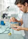 Young male tech cleans faulty computer processor. In hardware repair workshop Royalty Free Stock Image