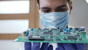 Young male tech or engineer repairs electronic equipment. Young male tech or engineer in a protective medical mask on the face and blue gloves repairs electronic stock video footage