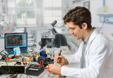 Young male tech or engineer repairs electronic equipment in rese. Young energetic male tech or engineer repairs electronic equipment in research facility Stock Photography
