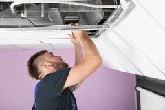 Young male technician checking air conditioner. Indoors Stock Photos
