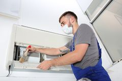 Young male technician cleaning air. Conditioner indoors Stock Photos