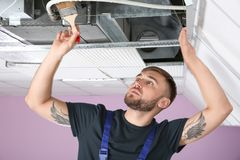 Young male technician cleaning air conditioner. Indoors Stock Photo
