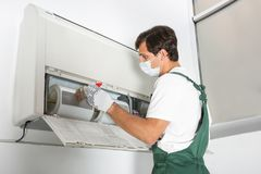 Young male technician cleaning air conditioner. Indoors royalty free stock photography