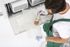 Young male technician cleaning air conditioner. Indoors Stock Image