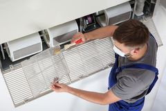 Young male technician cleaning air conditioner. Indoors Stock Photos