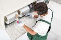 Young male technician cleaning air conditioner. Indoors Royalty Free Stock Image